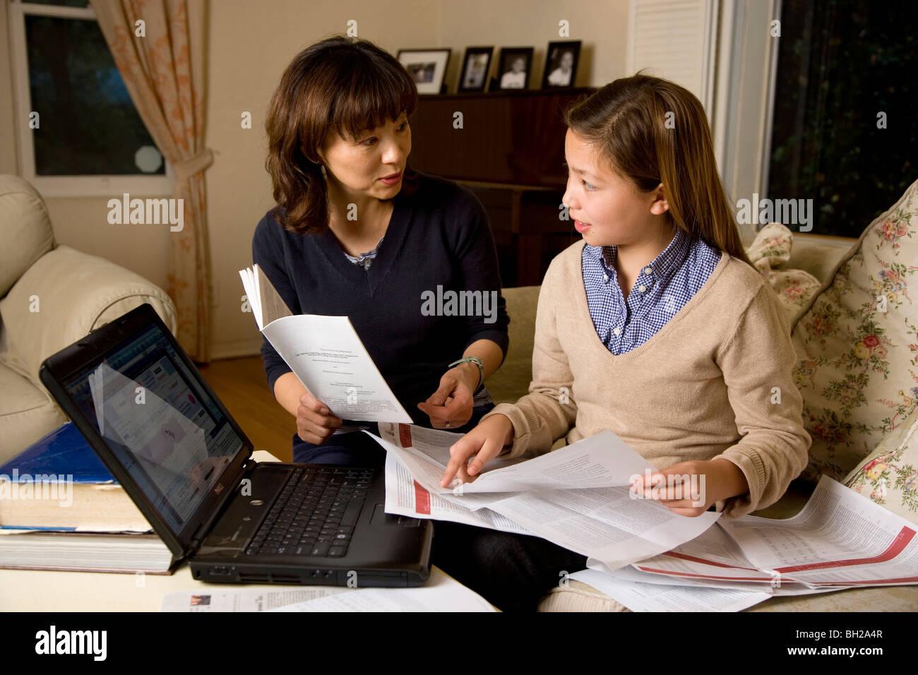 Koreanischen Mutter Tochter Koreanisch/weiß mit Computer investieren und investieren Berichte zu Hause reden. Stockfoto