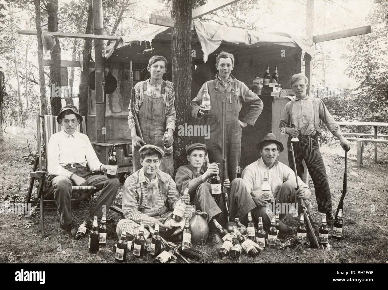 Sieben bewaffneten jungen umgeben von Dutzenden von Schnapsflaschen Stockbild