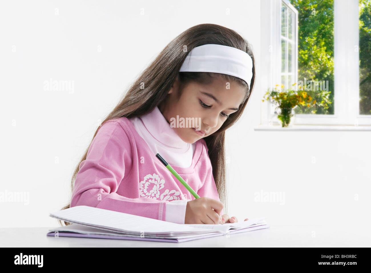 Mädchen in ein Notizbuch schreiben Stockbild