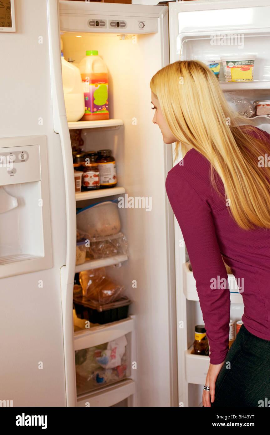 Junge blonde Mädchen suchen in offener Küche Kühlschrank nach etwas ...