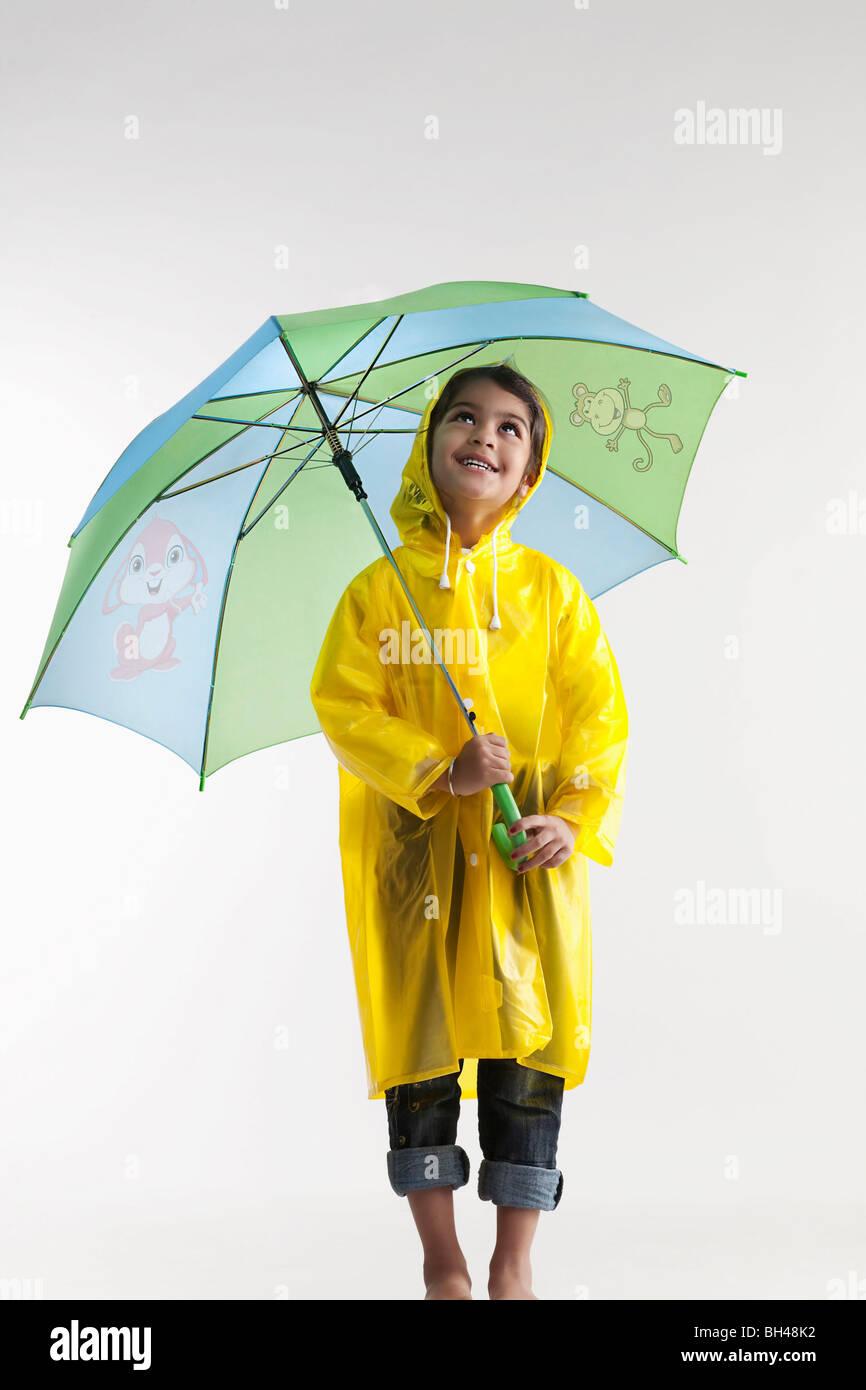Mädchen trägt einen Regenmantel und hält einen Regenschirm Stockbild