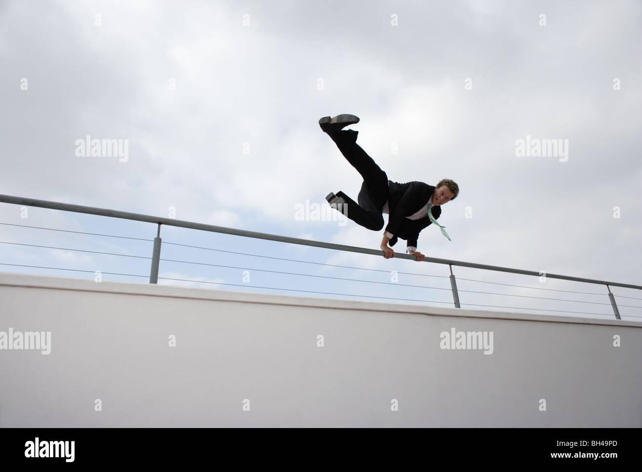 Junger Geschäftsmann springen über eine Mauer in der Stadt Stockbild