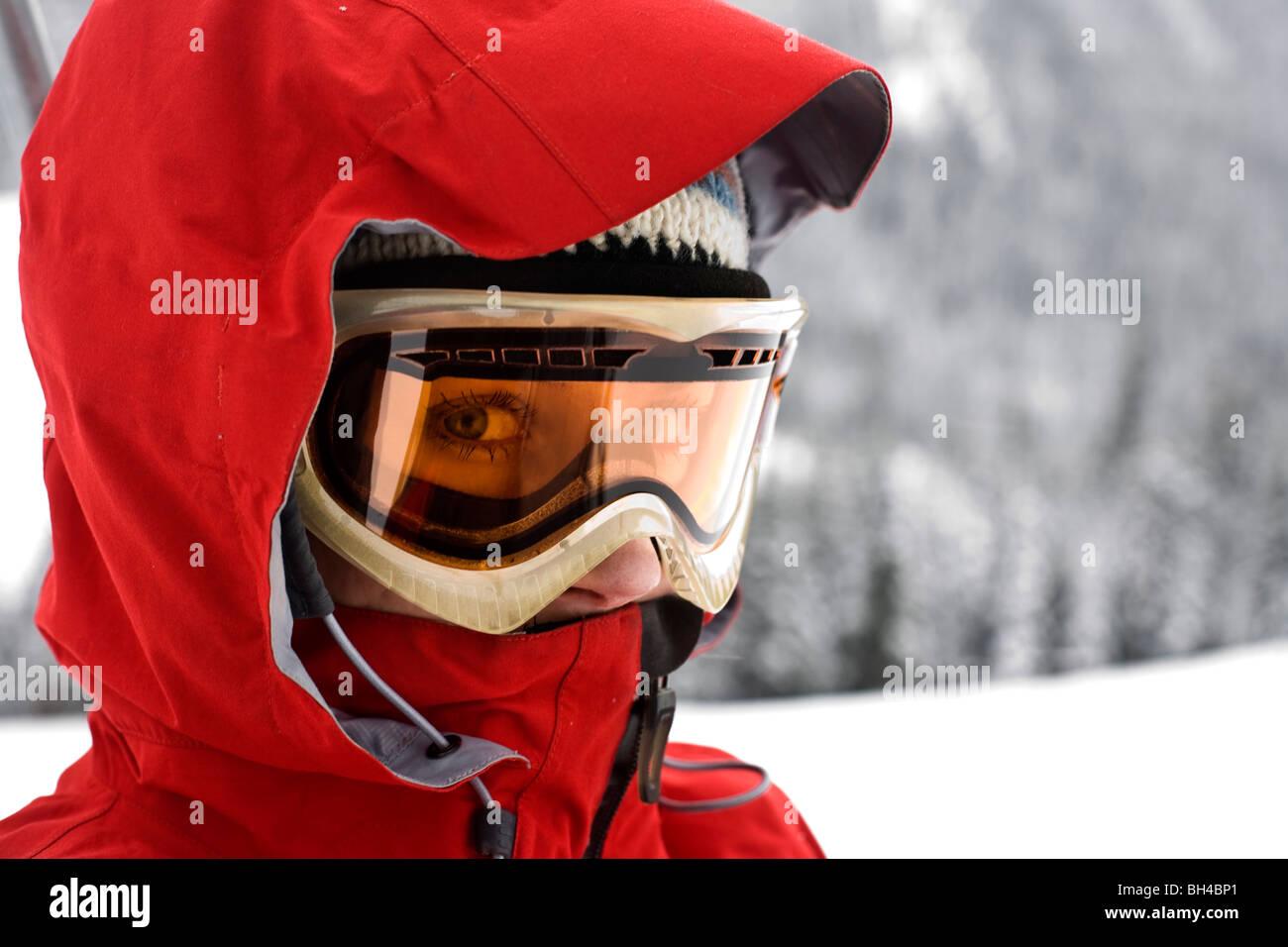 Ein close-up Portrait einer Frau trägt einen roten Skipiste Mantel, Schutzbrille und ein direkter Blick in Stockbild