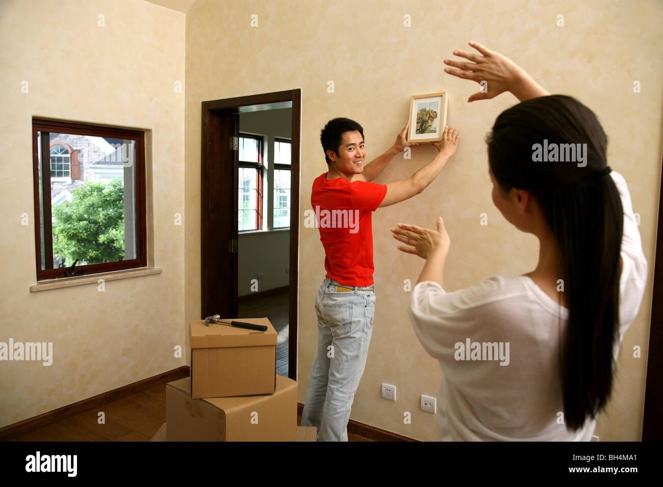 Chinesische junge Paar einen Bilderrahmen an der Wand aufhängen ...