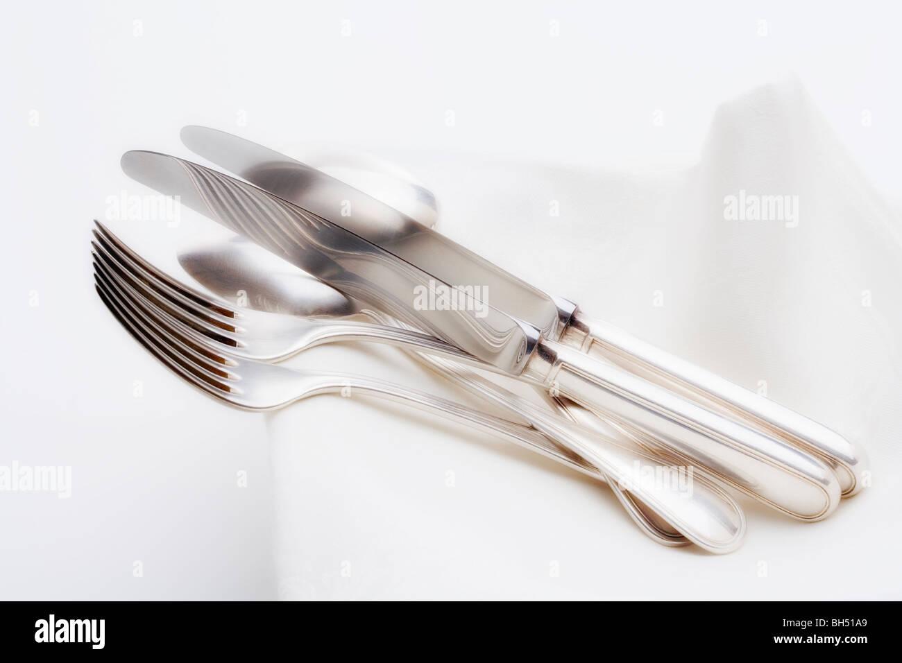 Besteck - Nahaufnahme des eleganten Messer Gabel und Löffel auf dem weißen Tuch Stockbild