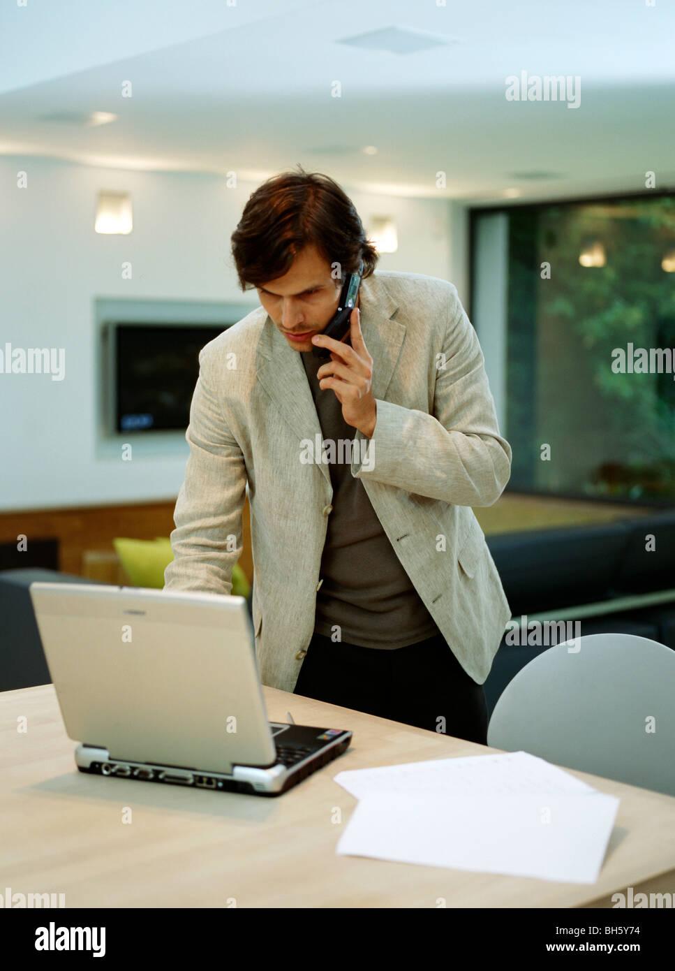 Ein junger trendigen Mann arbeitet von zu Hause Stockbild