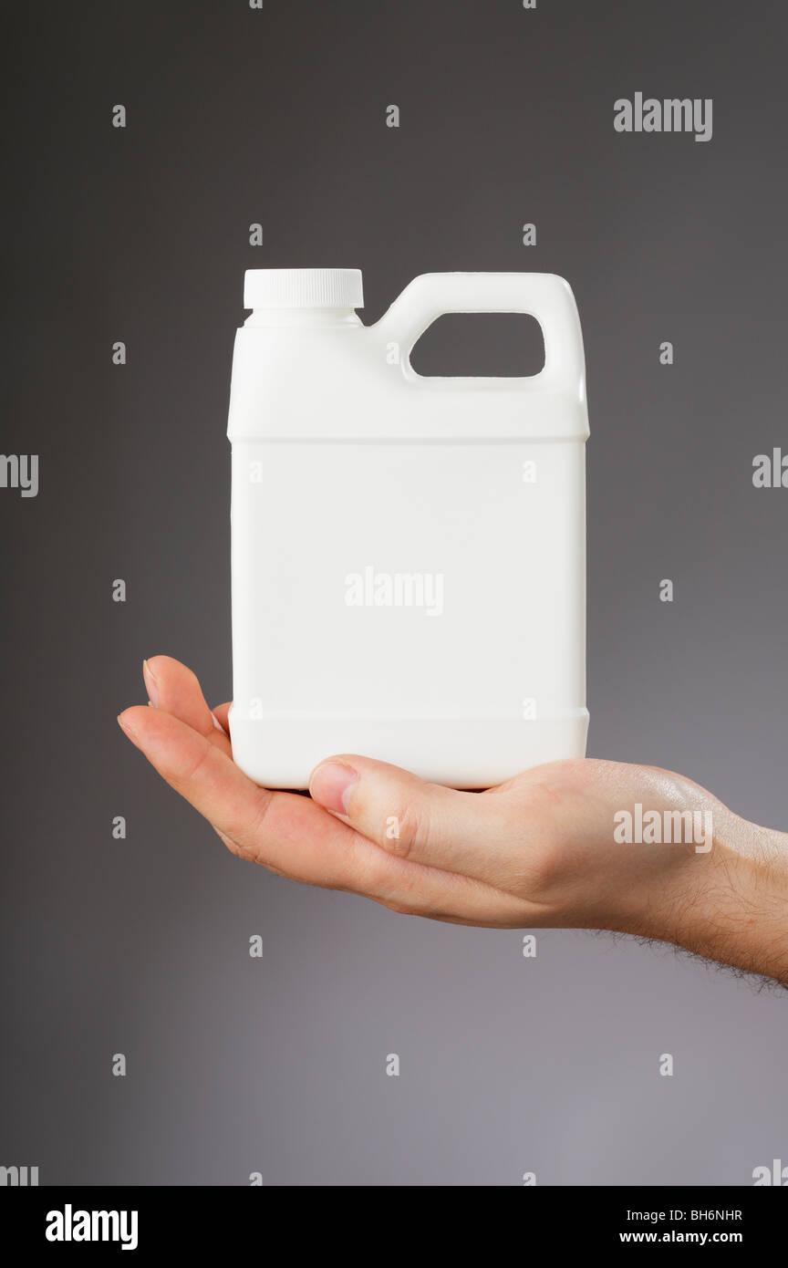 Hand mit einem kleinen weißen leeren Behälter Stockbild