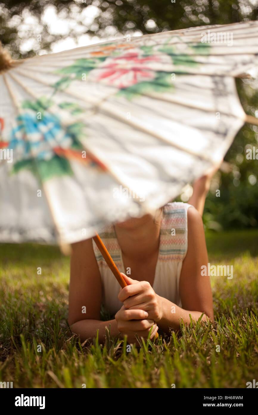 Eine Mädchen entspannt auf dem Rasen unter ihrem chinesischen Dach. Stockbild