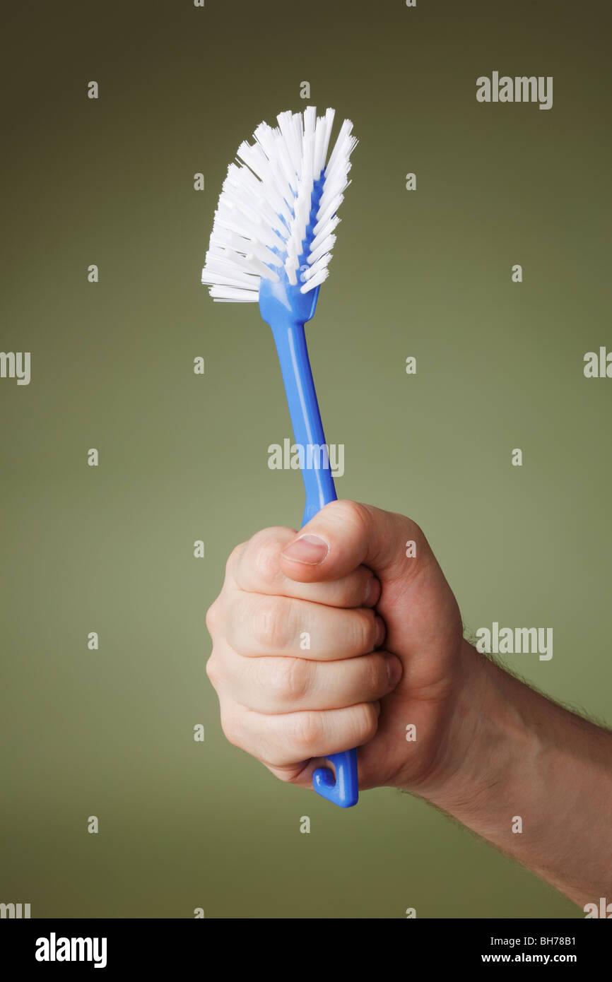Eine Hand hält einen Gericht-Pinsel Stockbild