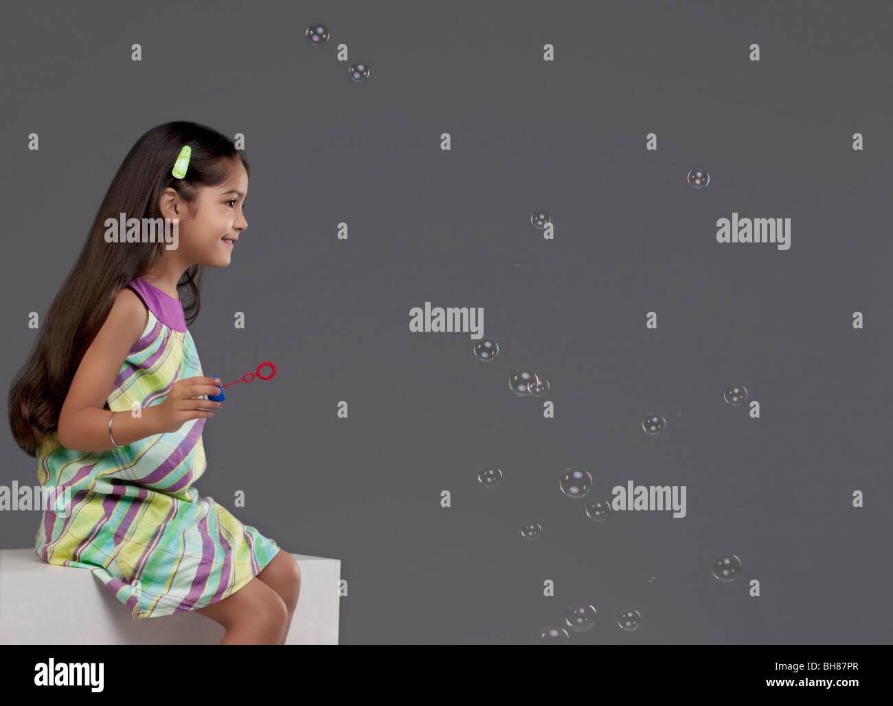 Mädchen spielen mit Luftblasen Stockbild