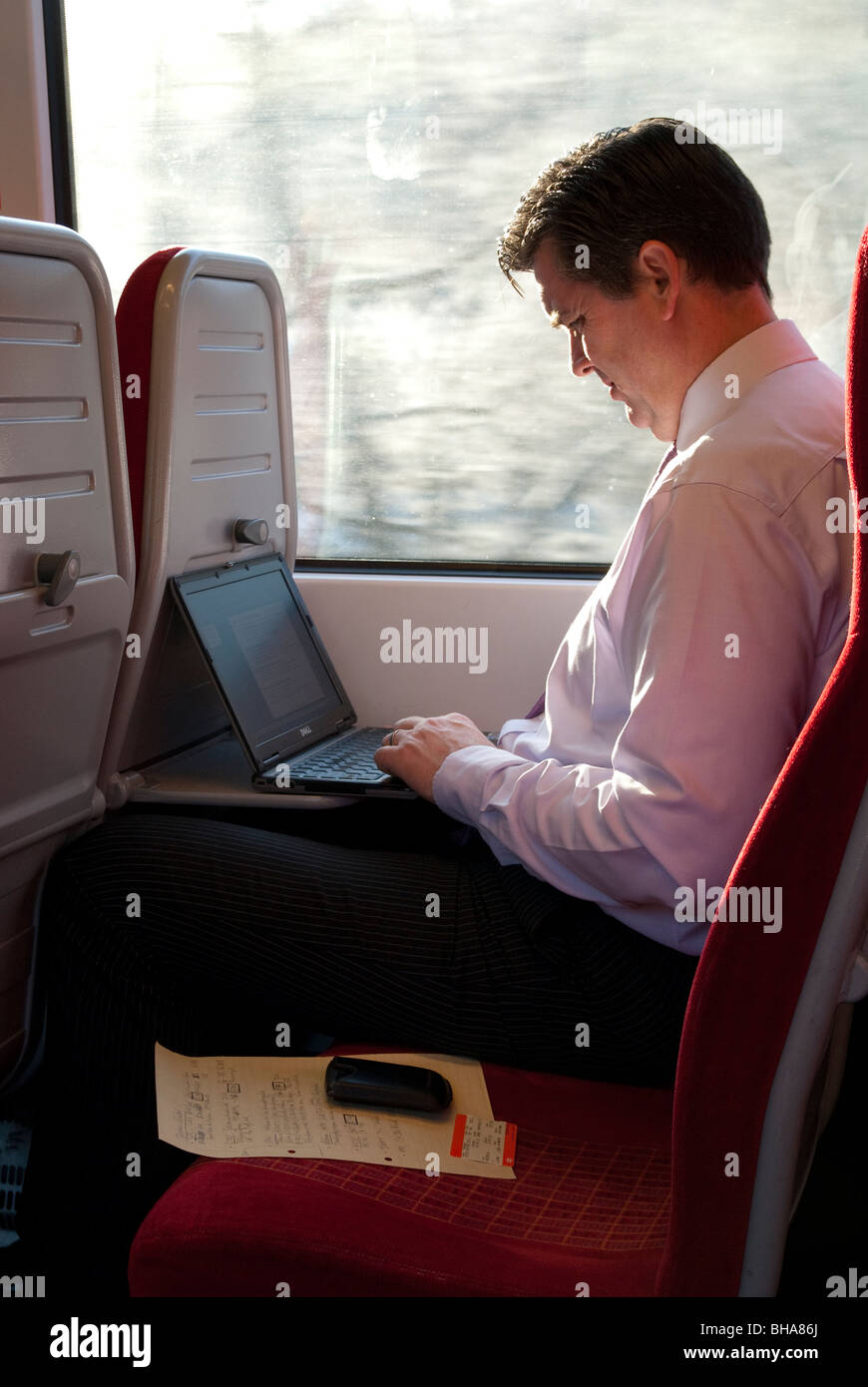 Business Mann Pendler mit Laptop-Computer auf Passagier-Bahnreise Stockfoto