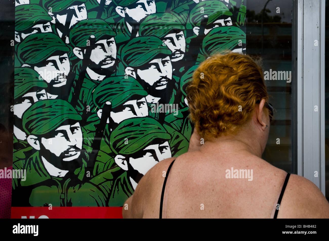Eine kubanische Frau Blick durch ein Schaufenster von Fidel Castros Propagandaplakat in Santiago De Cuba, Kuba abgedeckt. Stockbild