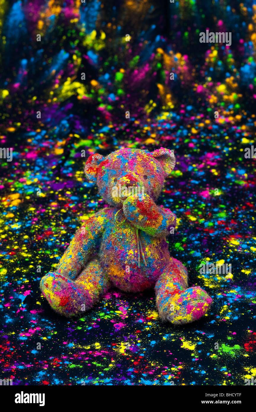 Teddy saß auf einem schwarzen Tuch in farbigen Pulver bedeckt. Noch immer leben Stockbild