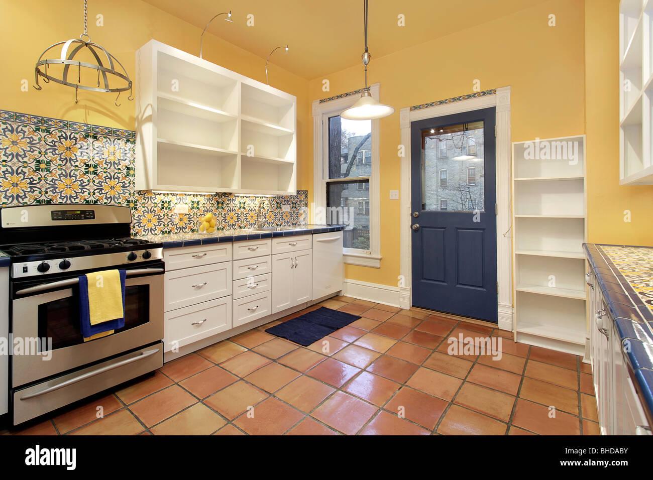 Küche in Vorstadthaus mit Terrakotta Boden Fliesen und gelben Wänden ...