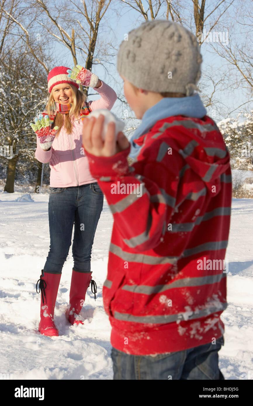 Mutter und Sohn mit Schneeballschlacht In Schneelandschaft Stockfoto