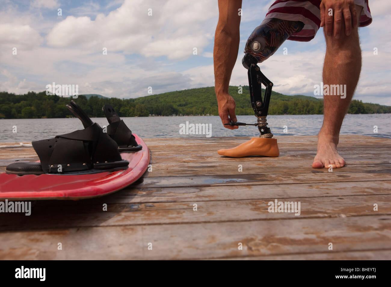 Behinderte Sportler sein künstliche Bein auf einem Dock anpassen Stockbild