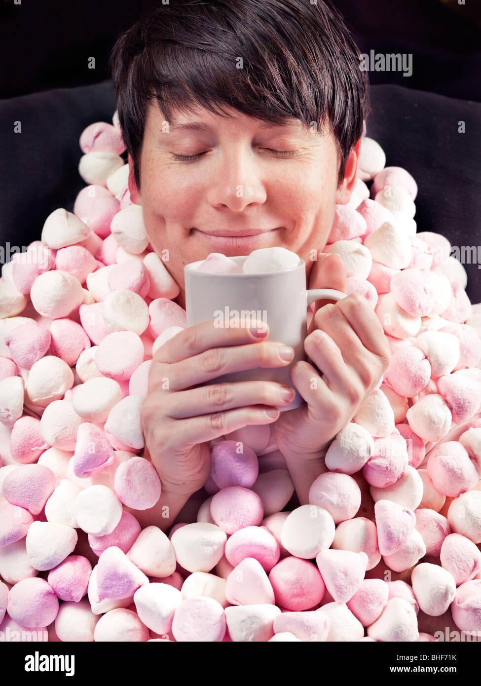 Frau mit Marshmallow-Decke und heiße Schokolade Stockbild