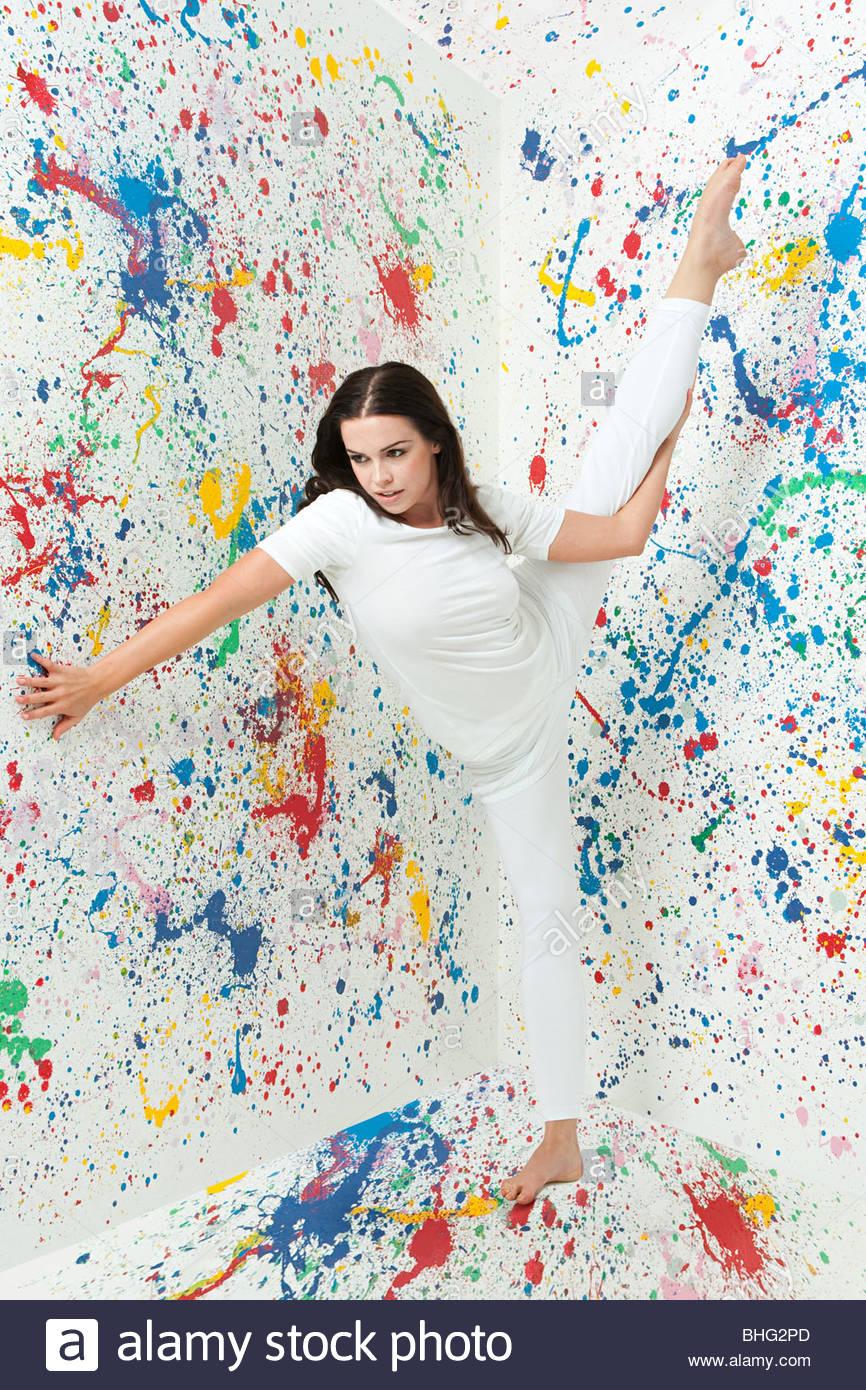Frau mit Bein angehoben und Wände mit Farbe bedeckt Stockbild