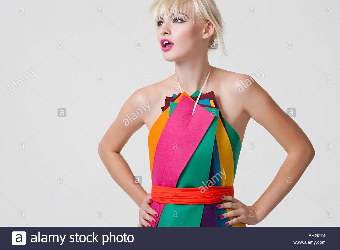 Junge Frau im Kleid aus farbigen Bändern Stockbild