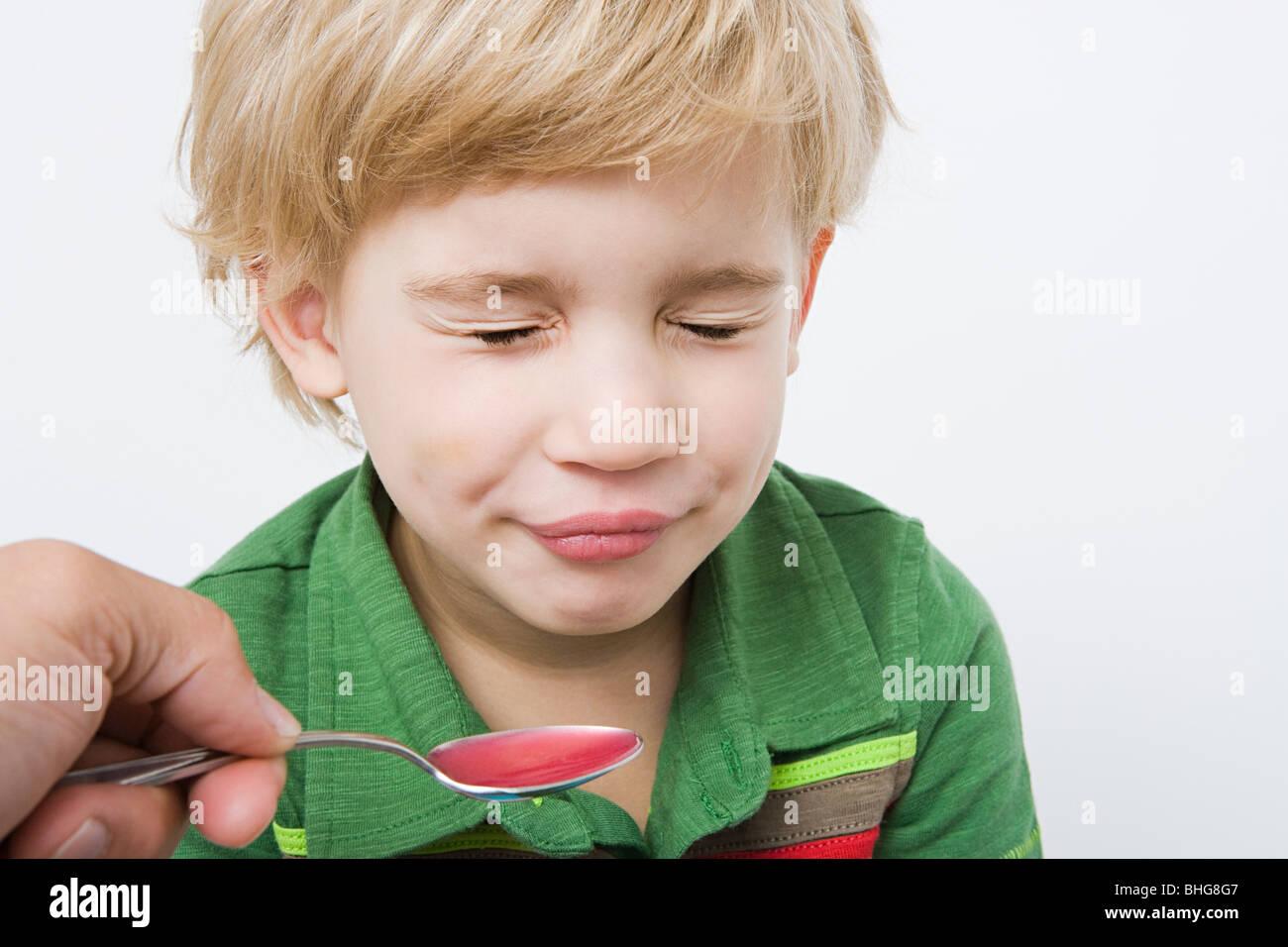 Junge und Löffel der Medizin Stockbild