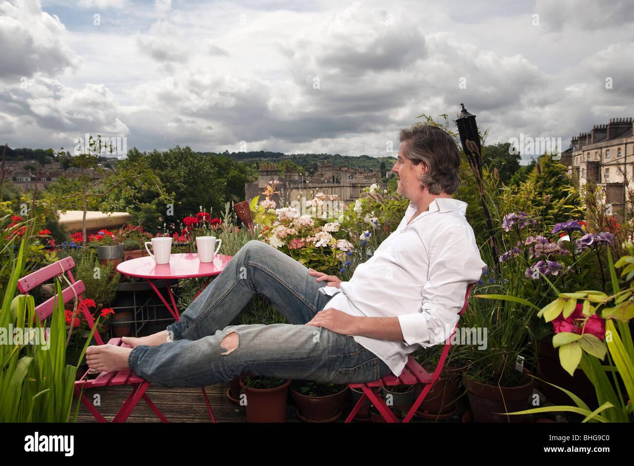 Mann sitzt auf Balkon Stockbild