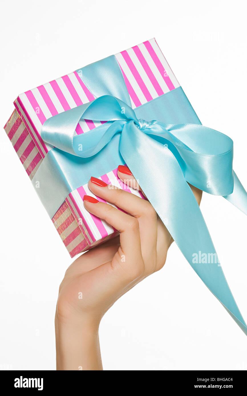 Weibliche Hand hält ein Geschenk Stockbild