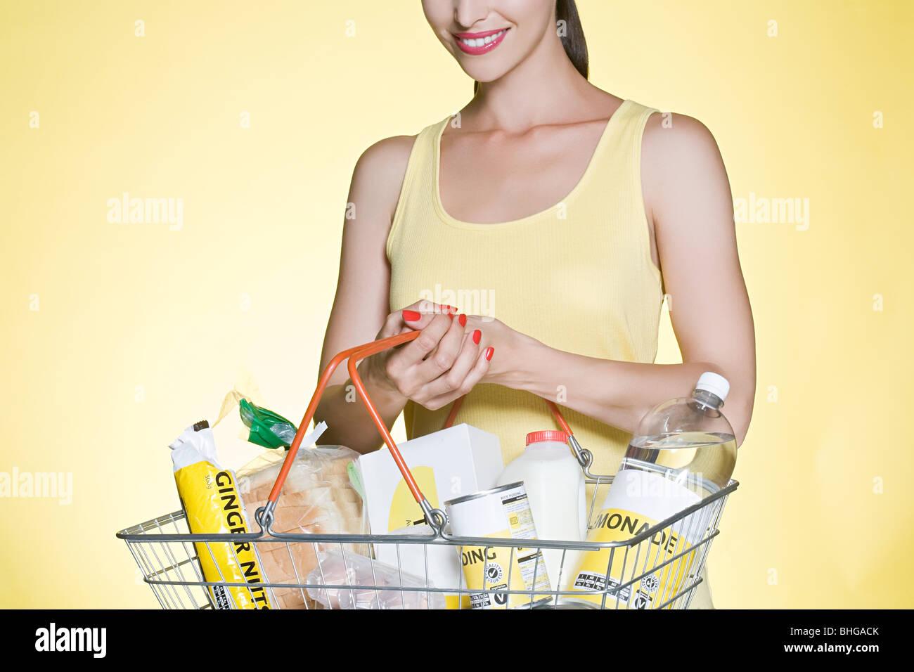 Frau mit Grundnahrungsmittel in Korb Stockbild