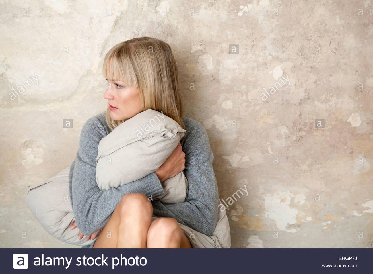 Frau sitzt am Boden mit Kissen Stockbild