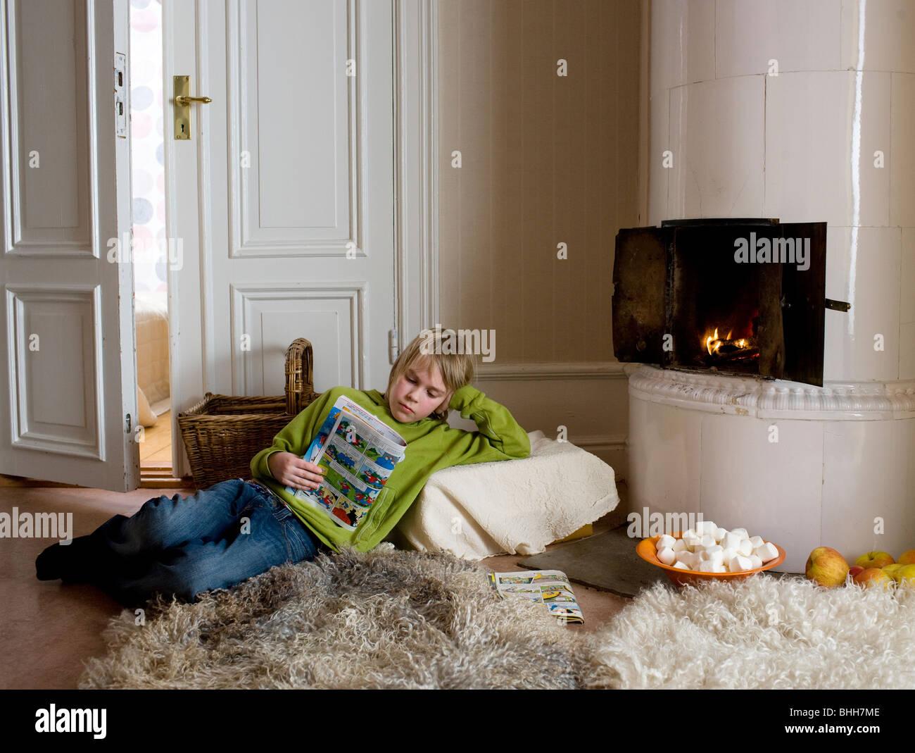 Junge liest von einem Kachelofen, Schweden. Stockbild