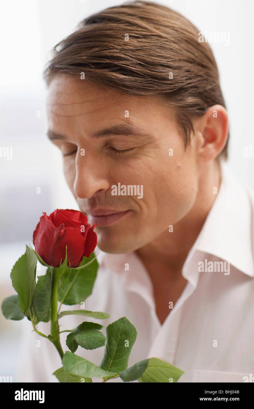 gut aussehender Mann und der Duft einer Rose Stockbild