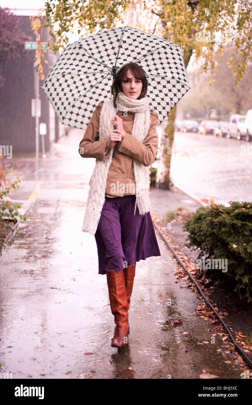 Frau zu Fuß im Regen unter Dach Stockbild