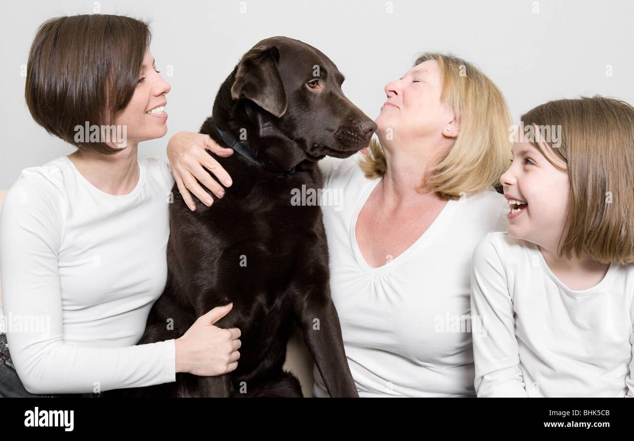 Schuss von drei Generationen einer Familie lachen mit ihrem Hund Stockbild