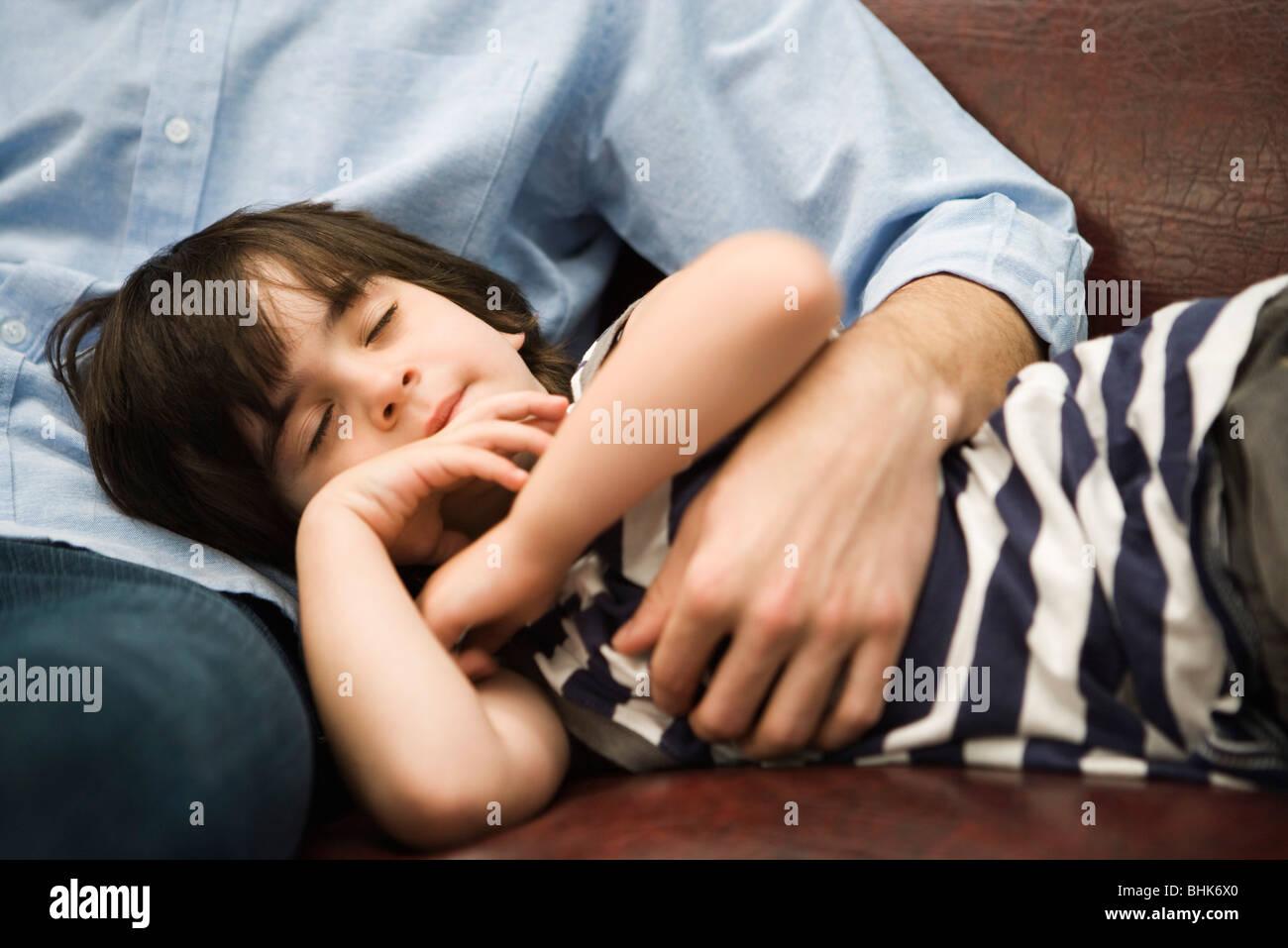 Kleiner Junge mit Kopf in des Vaters Schoß schlafen Stockfoto