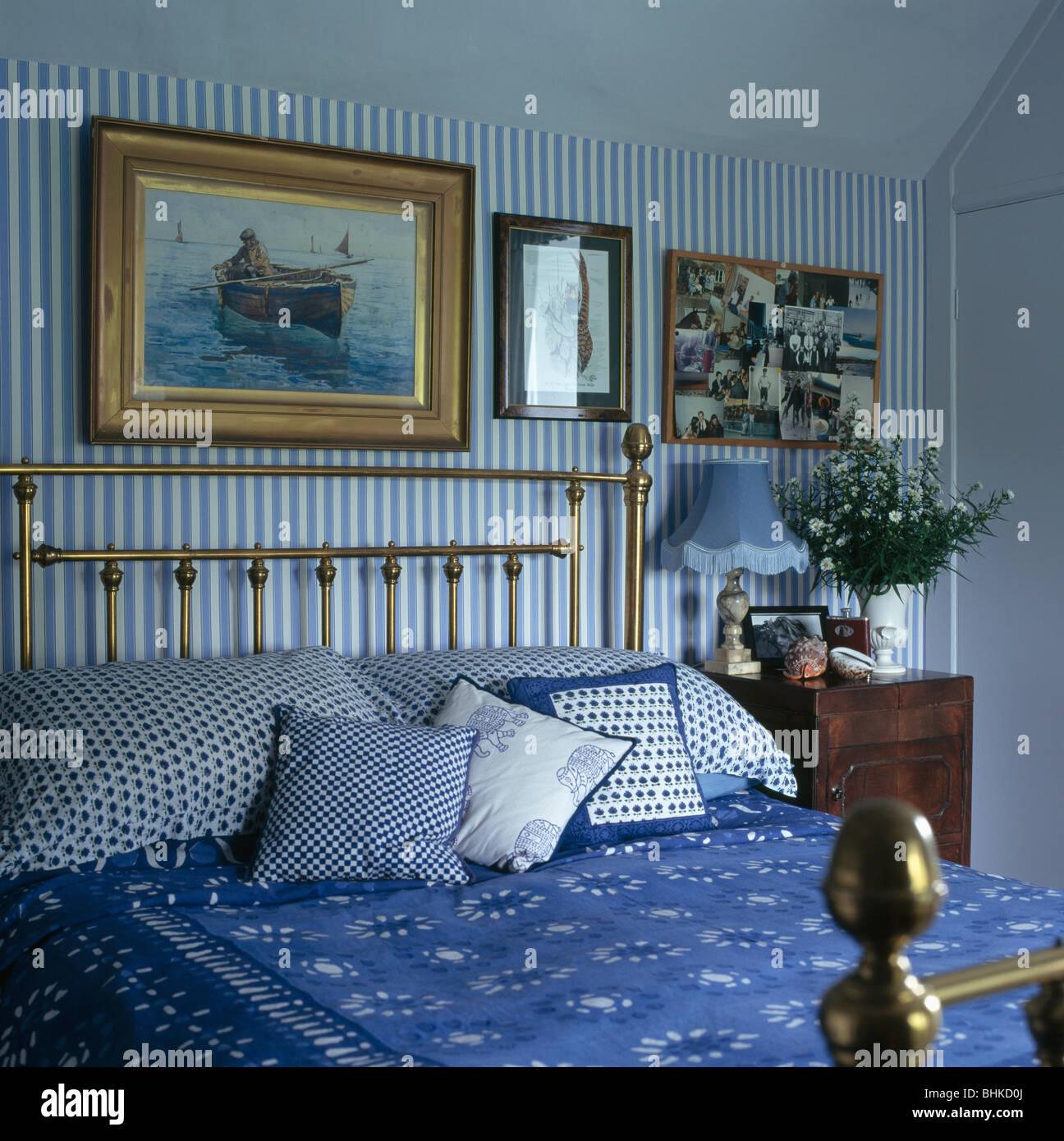 Alte Gemälde An Der Wand über Dem Antiken Messing Bett Mit Blauen Kissen  Und Bettdecke Im Schlafzimmer Mit Blau + Weiß Gestreifte Tapete