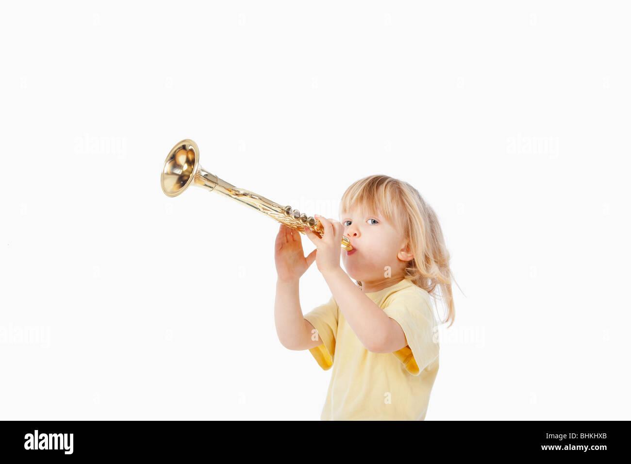 Junge mit langen blonden Haaren mit Spielzeug Trompete spielen Stockfoto