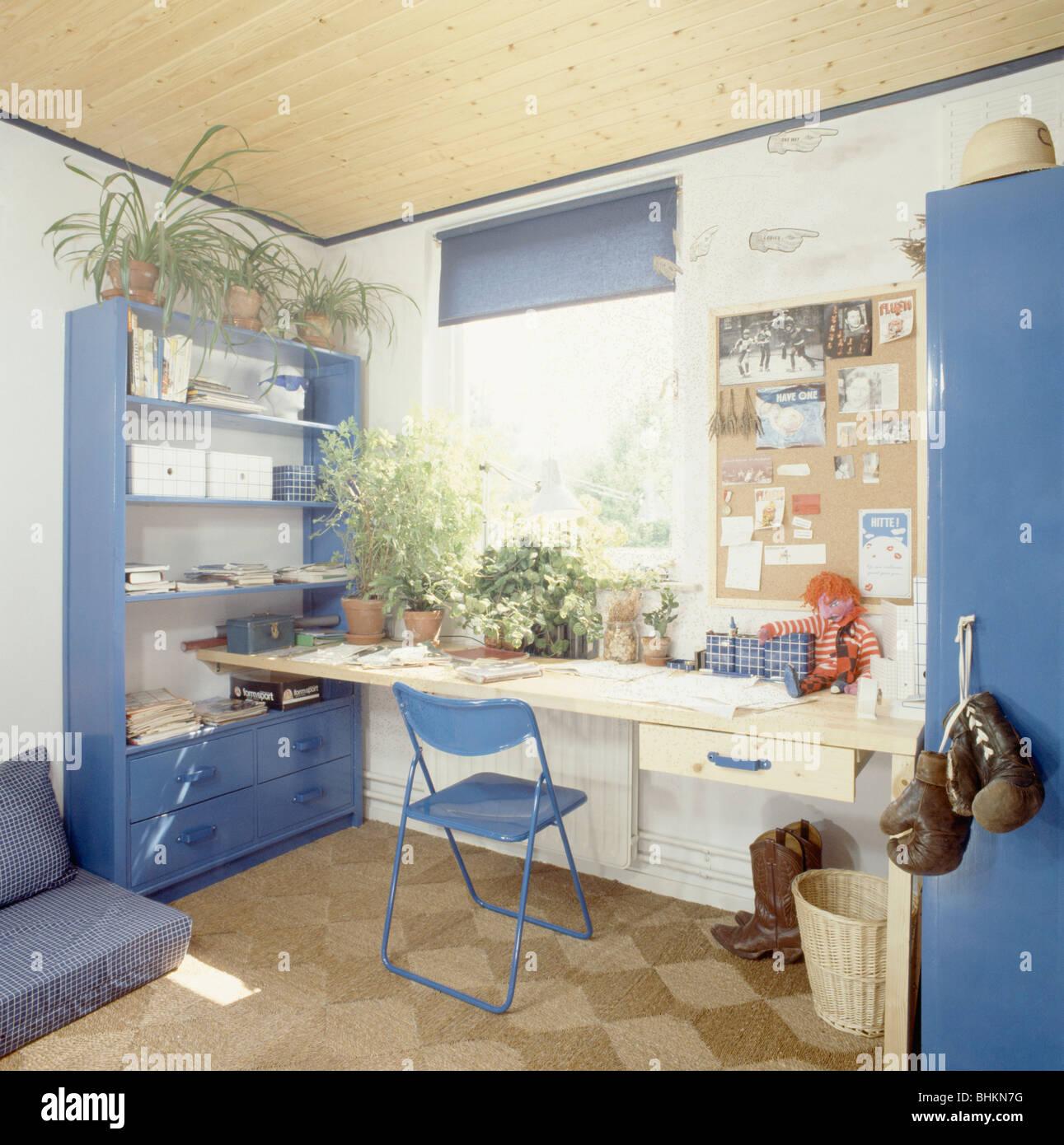 Freistehende Regale blauer stuhl und einfachen hölzernen schreibtisch im jugendzimmer
