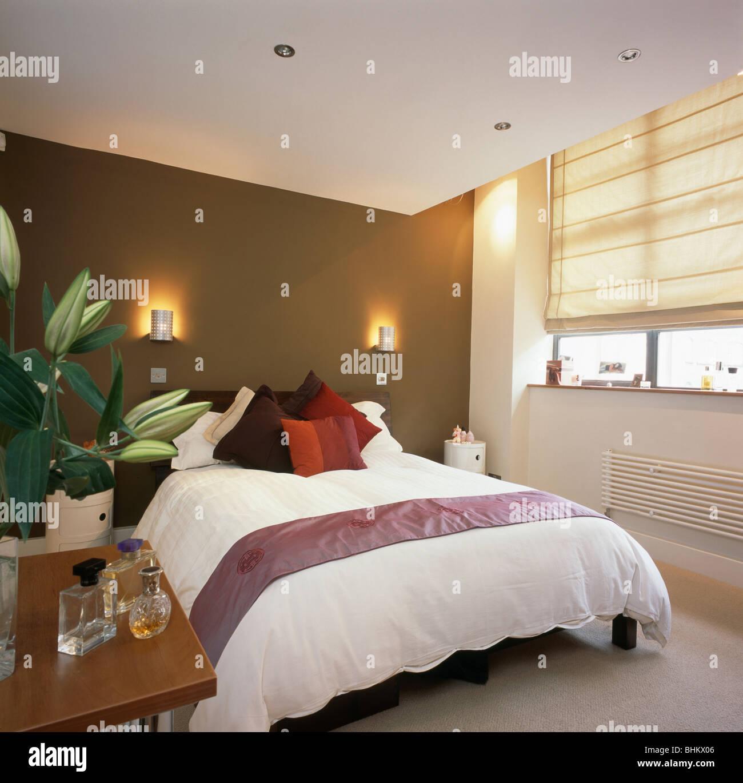 Wandleuchten auf braune Wand über dem Bett mit weißen Bettdecke in ...