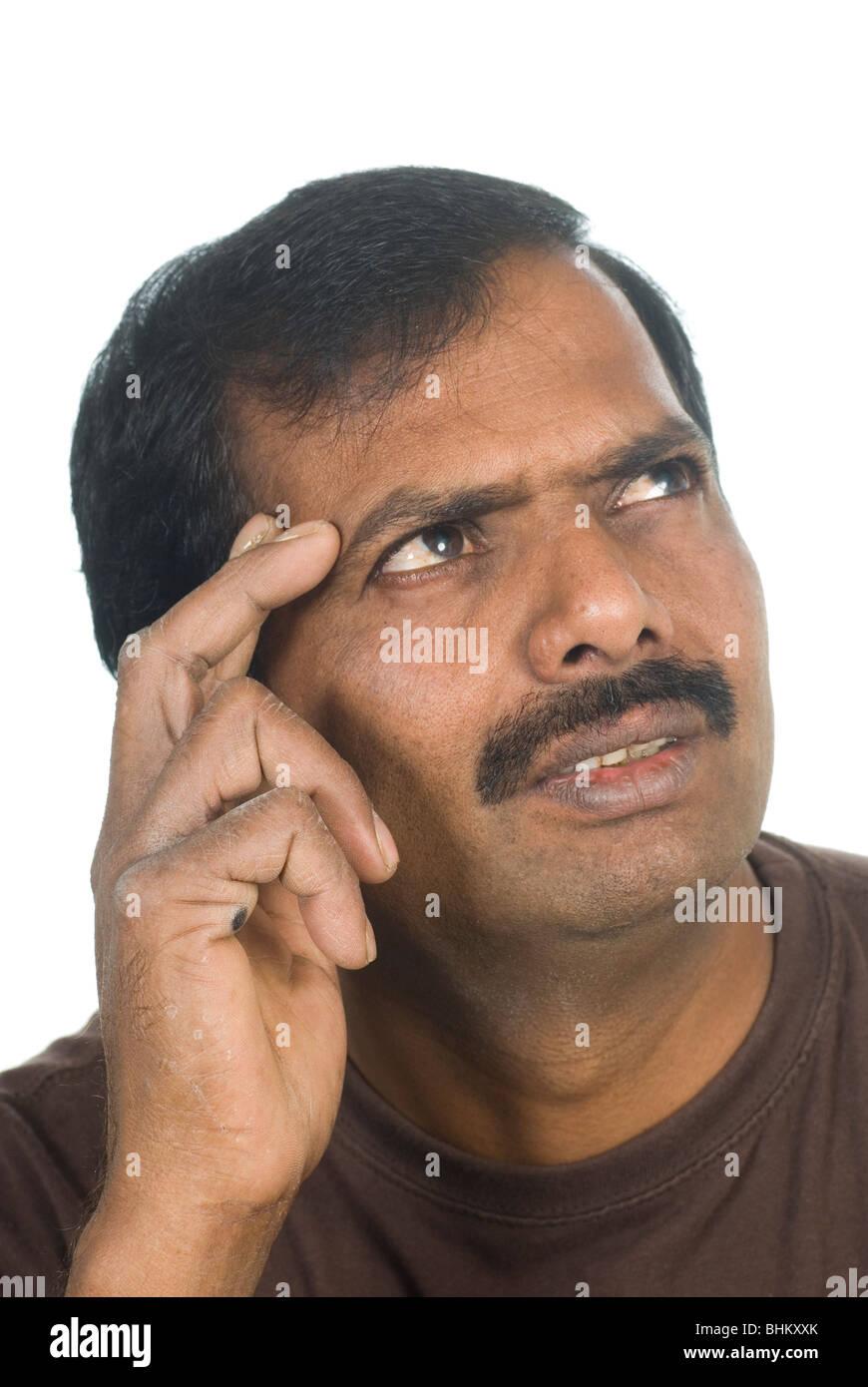 Indischer Mann versucht, etwas gegen einen weißen Hintergrund erinnern Stockbild