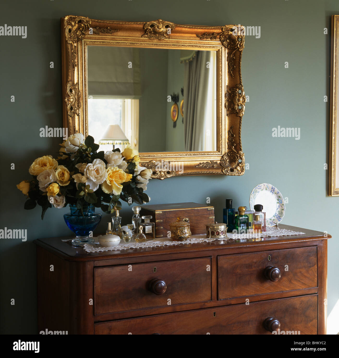 Nahaufnahme der große vergoldete Spiegel über Vase mit gelben Rosen ...