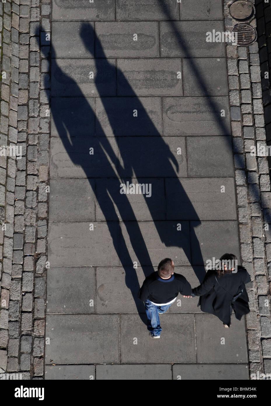 Ein paar haltende Hand wirft einen langen Schatten Stockbild