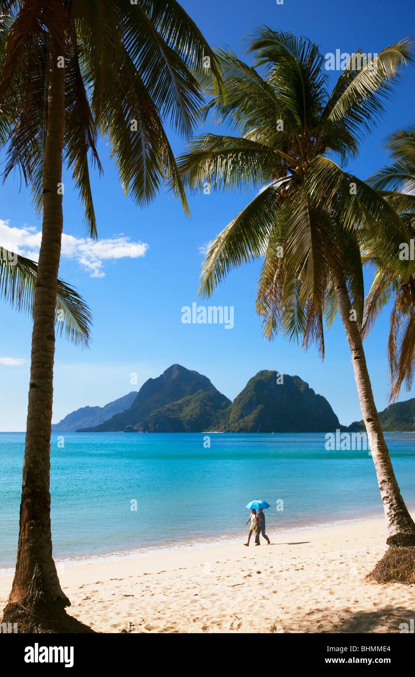 Blick durch Palmen von zwei Menschen zu Fuß auf Strand, Meer und Inseln; Las Reetdächern; El Nido; Bacuit; Stockbild