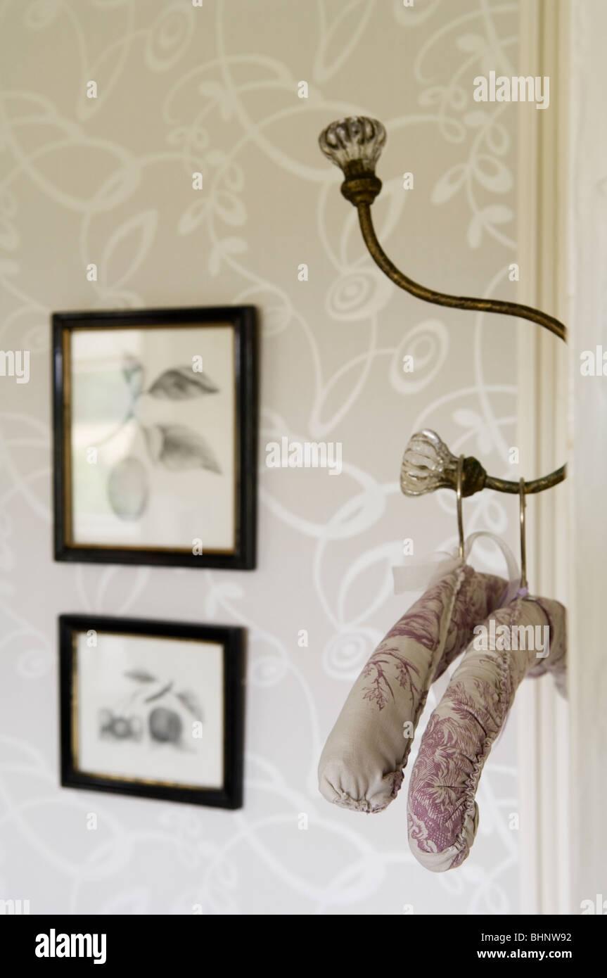 altmodische gepolsterten Kleiderbügel auf verzierte Garderobenhaken Stockbild