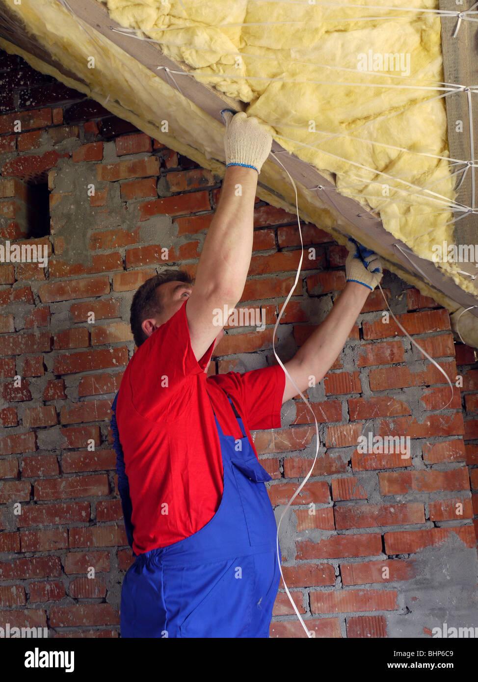 Bauarbeiter, die thermisch isolierende Haus Dachboden mit Steinwolle Stockbild