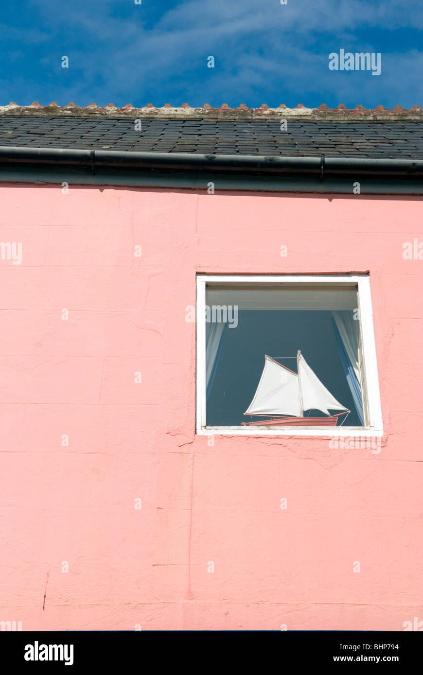 eine Modellyacht mit Segel in eine Fensterbank im Haus mit rosa Fassade Fenster positioniert Stockbild