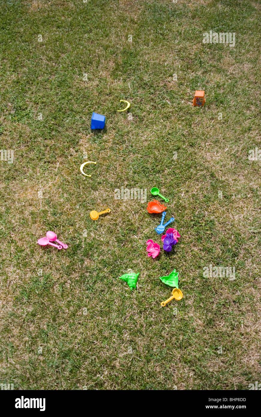 eine Auswahl an bunten Kinder Plastikspielzeug liegen verstreut auf einem Rasen in einem privaten Garten Stockbild