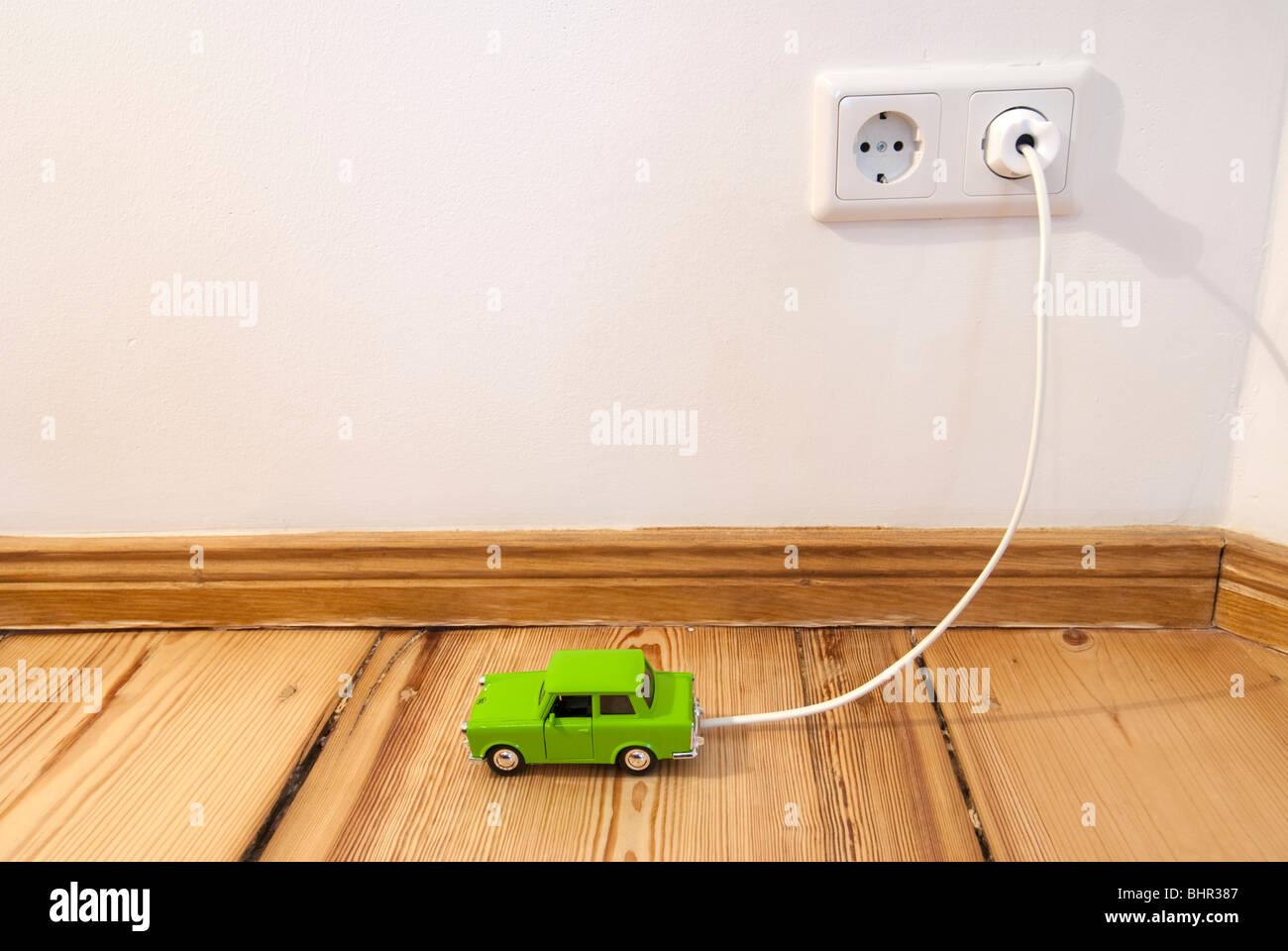 Konzept der elektrische Spielzeugauto wird durch steckbaren Anschluss an Stromversorgung im Haus aufgeladen Stockbild