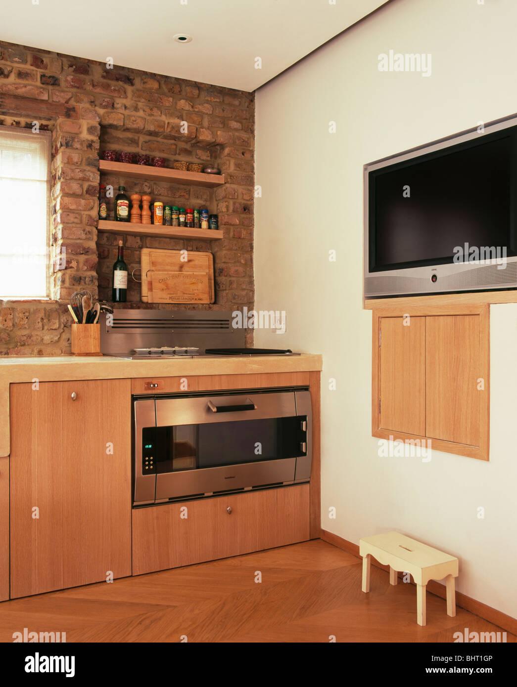 Große Fernseher eingebaut Wand in der modernen Küche mit hellem Holz ...