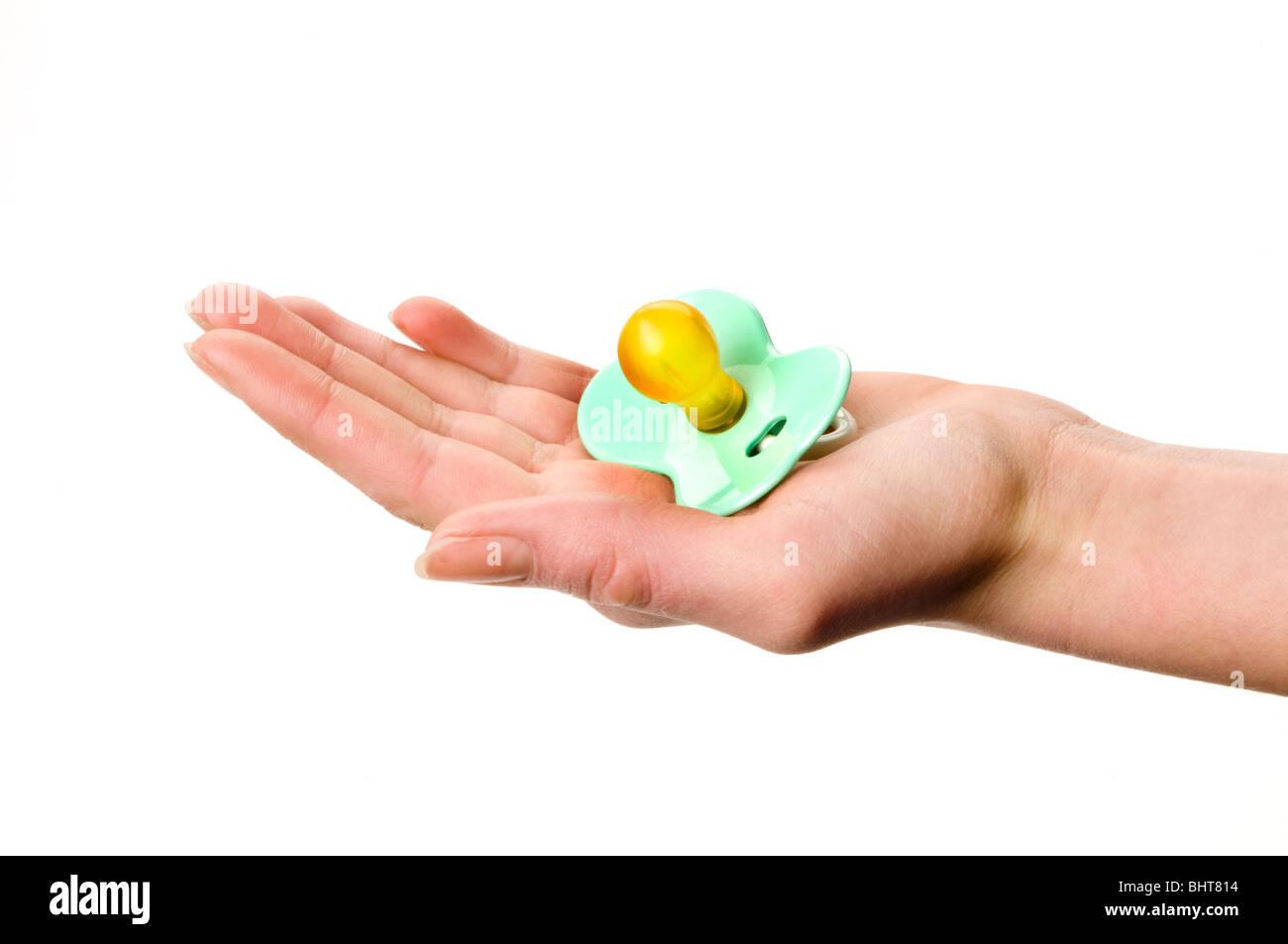 Hand hält Baby Schnuller Stockbild