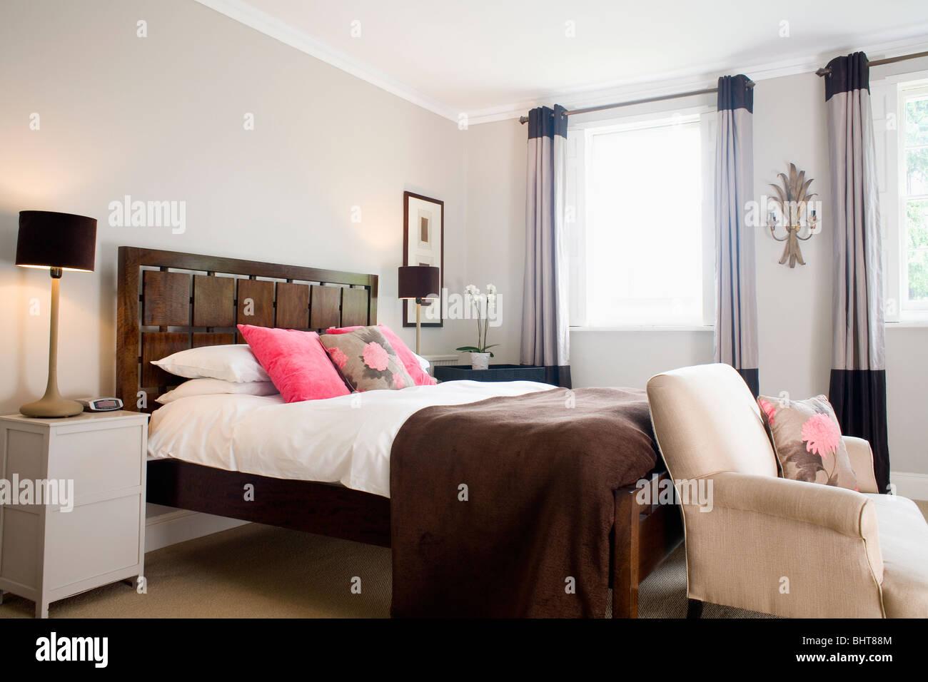 Tief Rosa Kissen Und Braun Zu Werfen, Auf Dem Bett Mit Kopfteil Aus Holz  Und Weißen Bettwäsche In Modernen Schlafzimmer Mit Cremefarbenen Sessel