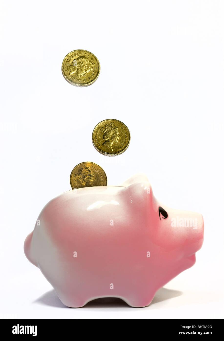 Pfund-Münzen und rosa Sparschwein Stockbild